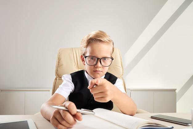 Blond kaukaska chłopiec siedzi przy biurkiem w biurze w szkłach i wskazuje w kierunku kamery Darmowe Zdjęcia