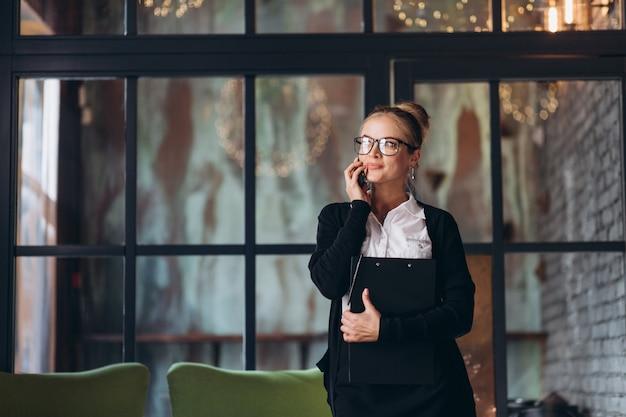 Blond Kobieta Biznesu Siedzi Na Obszarze Roboczym I Za Pomocą Laptopa W Biurze, Patrzy Na Folder Z Dokumentami, Rozmawia Przez Telefon I Pije Kawę. Premium Zdjęcia