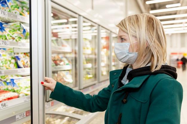 Blond Kobieta W Masce Medycznej Robi Zakupy W Supermarkecie. Samoizolacja W Pandemii. Premium Zdjęcia