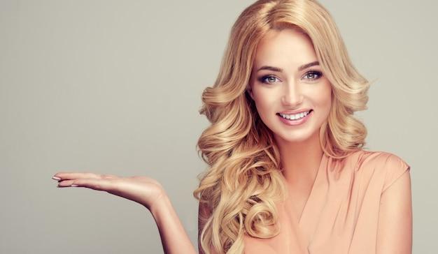 Blond kobieta z kręconymi włosami pokazuje swój produkt Premium Zdjęcia