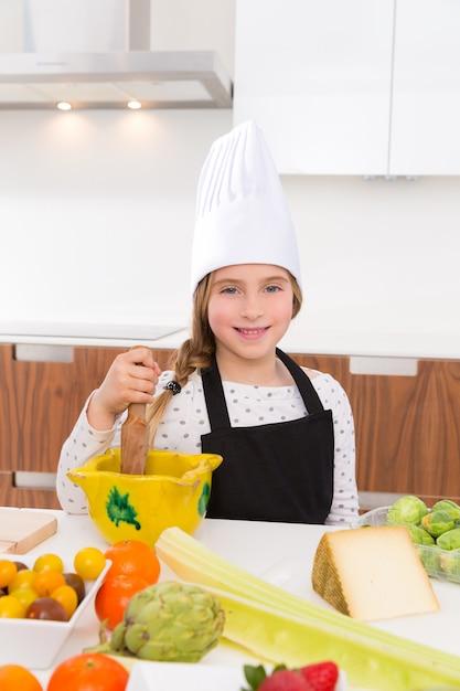 Blond miłej dziewczyny młodzieżowy szef kuchni na countertop Premium Zdjęcia