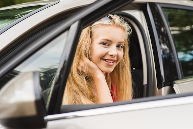 Blond Nastolatka Siedzi W Samochodzie I Uśmiecha Się Premium Zdjęcia