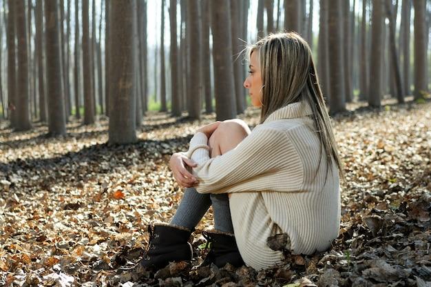 Blonde Kobieta Siedzi Na Liściach W Lesie Darmowe Zdjęcia