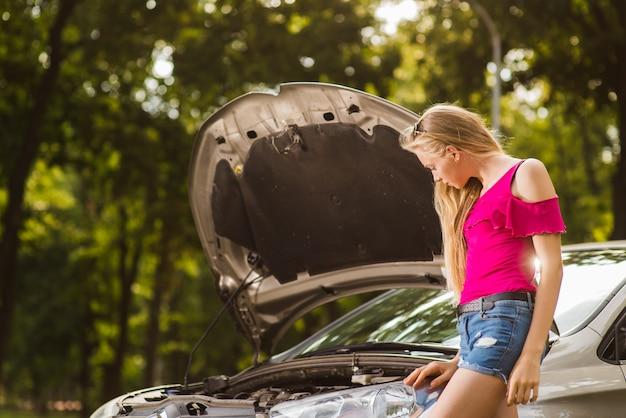 Blondy Smutna Kobieta Blisko Otwartego Samochodu Premium Zdjęcia