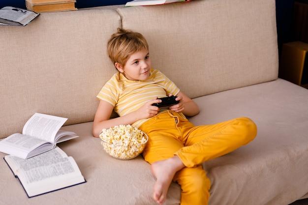 Blondyn Gra Zamiast Lekcji Padem I Zjada Popcorn. Premium Zdjęcia