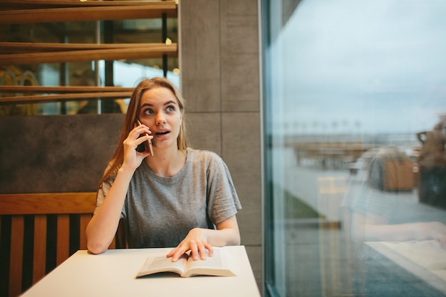 Blondynka Czyta Książkę I Rozmawia Przez Telefon W Jadalni Lub Restauracji Premium Zdjęcia