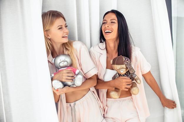 Blondynka i brunetka śmiejąc się w piżamie z zabawkami niedźwiedzie stojące na balkonie Premium Zdjęcia