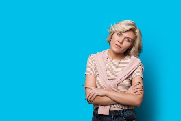 Blondynka Kaukaski Patrząc Do Kamery, Pozując Ze Skrzyżowanymi Rękami Na Niebieskiej ścianie Z Wolnej Przestrzeni Premium Zdjęcia