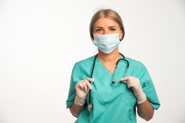 Blondynka Lekarz Noszenie Maski Na Twarz I Umieszczenie Stetoskopu Na Szyi Darmowe Zdjęcia