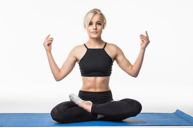 Blondynka Ma Czas Na Relaks Jogi Po ćwiczeniach Sportowych Na Podłodze, Siedząc Na Mapie Sportowej Darmowe Zdjęcia