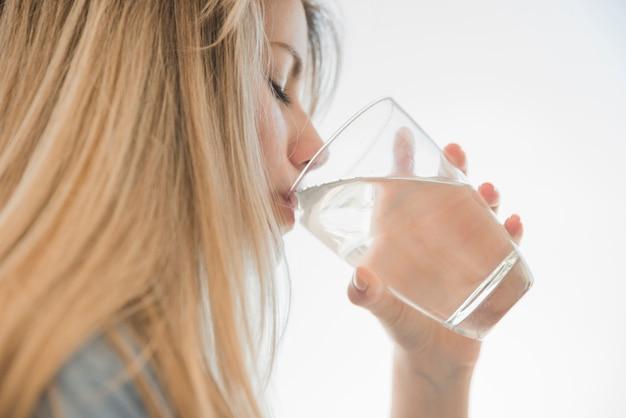 Blondynka pije szklankę wody Darmowe Zdjęcia