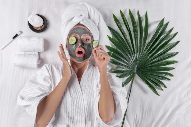 Blondynka Pozuje W Białym Płaszczu, A Na Głowie Ręcznik Z Glinianą Maską Premium Zdjęcia