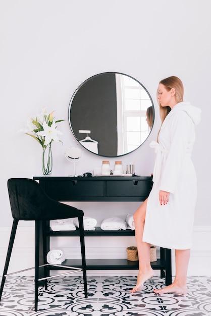 Blondynka pozuje w łazience z szlafrokiem Darmowe Zdjęcia
