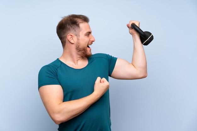 Blondynka sport mężczyzna na niebieską ścianą z kettlebell Premium Zdjęcia