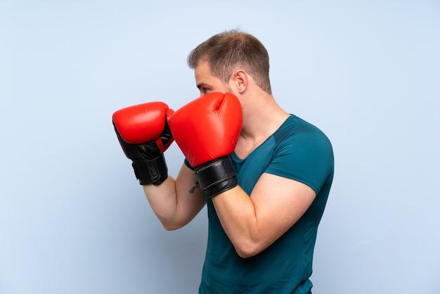 Blondynka sport mężczyzna na niebieską ścianą z rękawice bokserskie Premium Zdjęcia