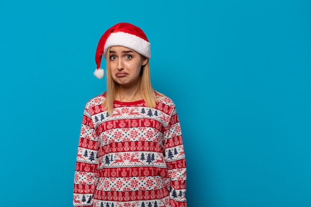 Blondynka W Czapce Mikołaja Czuje Się Smutna I Jęcząca Z Nieszczęśliwym Spojrzeniem, Płacze Z Negatywnym I Sfrustrowanym Nastawieniem Premium Zdjęcia