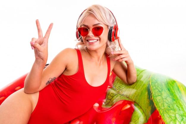 Blondynka W Czerwonym Kostiumie Kąpielowym I Okularach Przeciwsłonecznych Leży Na Materacu I Słucha Muzyki Na Słuchawkach Premium Zdjęcia