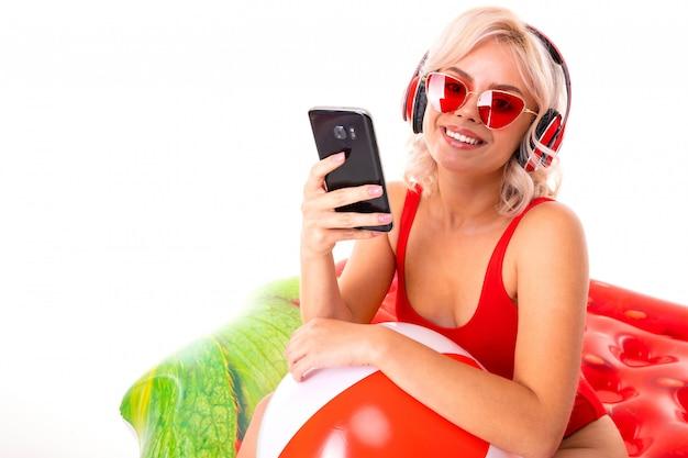 Blondynka W Czerwonym Stroju Kąpielowym I Okularach Przeciwsłonecznych Siedzi Na Materacu I Słucha Muzyki Na Słuchawkach Oraz Trzyma Telefon W Dłoniach Premium Zdjęcia