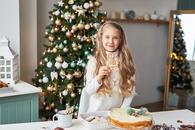 Blondynka w noworocznej kuchni z babeczkami i słodyczami Premium Zdjęcia