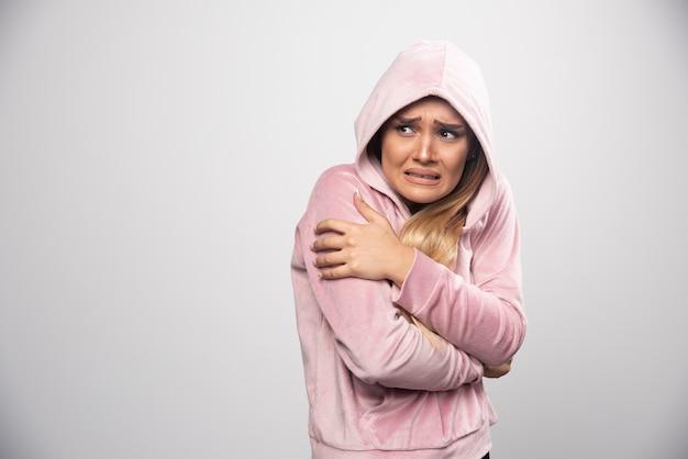 Blondynka W Różowej Bluzie Robi Przerażoną Minę W Bluzie Z Kapturem. Darmowe Zdjęcia