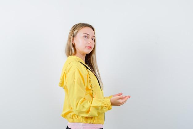 Blondynka W Różowej Koszulce I żółtej Kurtce, Rozciągając Ręce, Trzymając Coś I Wyglądając Poważnie Darmowe Zdjęcia