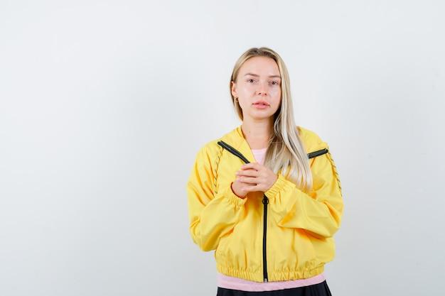 Blondynka W Różowej Koszulce I żółtej Kurtce, ściskając Ręce I Patrząc Poważnie Darmowe Zdjęcia