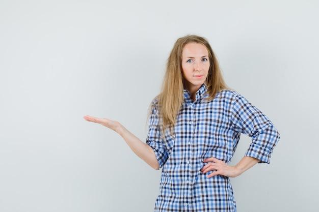 Blondynka Wita Lub Pokazuje Coś W Koszuli I Wygląda Pewnie. Darmowe Zdjęcia