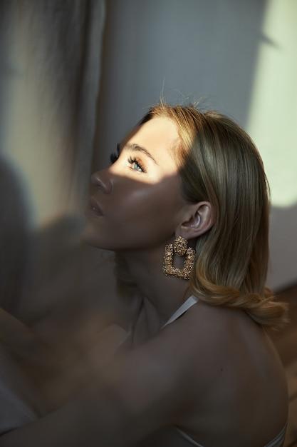 Blondynka Z Biżuterią W Uszach Siedzi Przy Oknie W Promieniach Wieczornego Słońca. Premium Zdjęcia