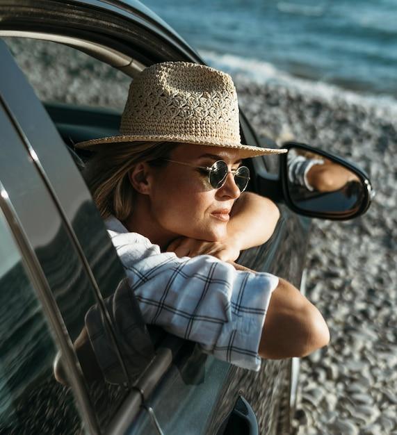 Blondynka Z Kapeluszem I Okularami Przeciwsłonecznymi, Patrząc Przez Okno Samochodu Darmowe Zdjęcia