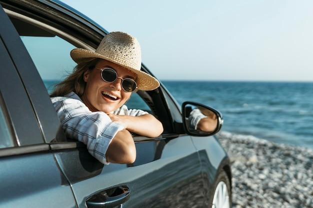 Blondynka Z Kapeluszem Patrząc Przez Okno Samochodu Darmowe Zdjęcia