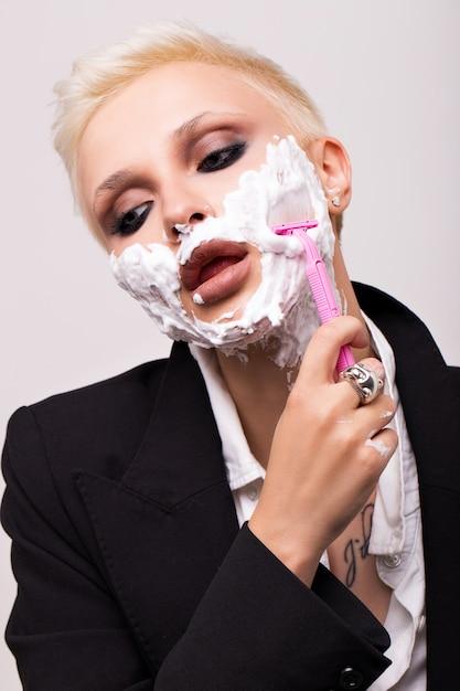 Blondynka z krótką fryzurą w czarnej kurtce z pianką do golenia na twarzy. Premium Zdjęcia