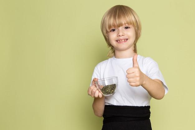 Blondynka Z Przodu Widok ślicznego Chłopca W Białej Koszulce Trzymającej Gatunki Na Biurku W Kolorze Kamienia Darmowe Zdjęcia