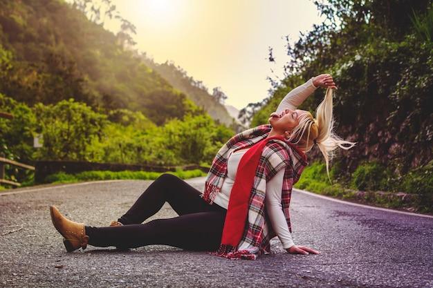 Blondynka, żyjąca Jak Szalona, Siedząca Na środku Drogi Z Wyciągniętym Językiem. Premium Zdjęcia