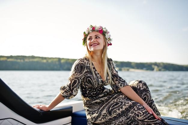 Blondynki dziewczyna w wianku obsiadaniu na jachcie przy kurnym przyjęciem. Premium Zdjęcia