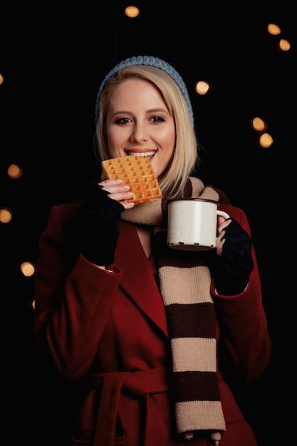 Blondynki Dziewczyna Z Filiżanką Kawy I Gofrem Premium Zdjęcia