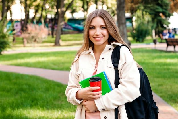 Blondynki dziewczyny uczeń chodzi w parku z notatnikiem i filiżanką kawy Premium Zdjęcia