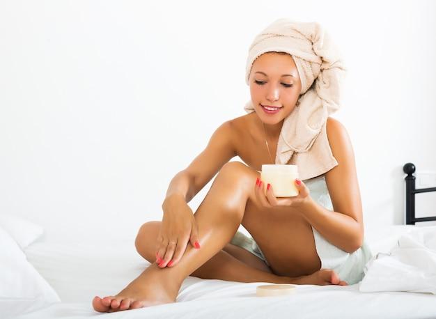 Blondynki kobieta używa kosmetyczną śmietankę Darmowe Zdjęcia