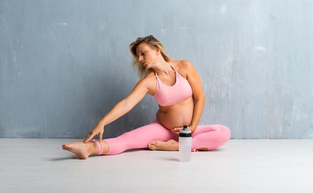 Blondynki kobieta w ciąży robi sportowi i rozciąga Premium Zdjęcia