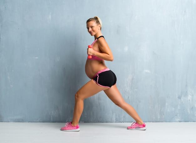 Blondynki kobieta w ciąży robi sportowi robi weightlifting Premium Zdjęcia