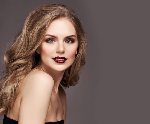 Blondynki kobieta z kędzierzawy piękny włosy ono uśmiecha się na popielatym tle. Premium Zdjęcia