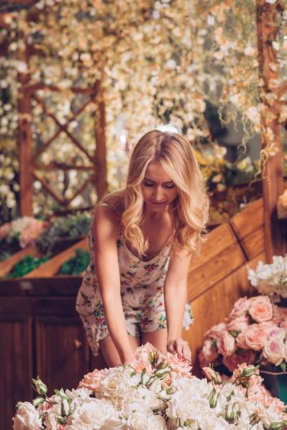 Blondynki młoda kobieta układa róże w kwiatu ogródzie Darmowe Zdjęcia