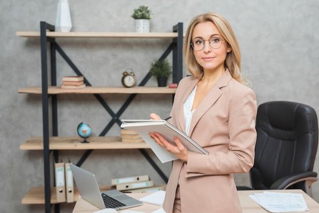 Blondynki młodej kobiety pozycja przed biurowego biura writing na ślimakowatym notatniku Darmowe Zdjęcia