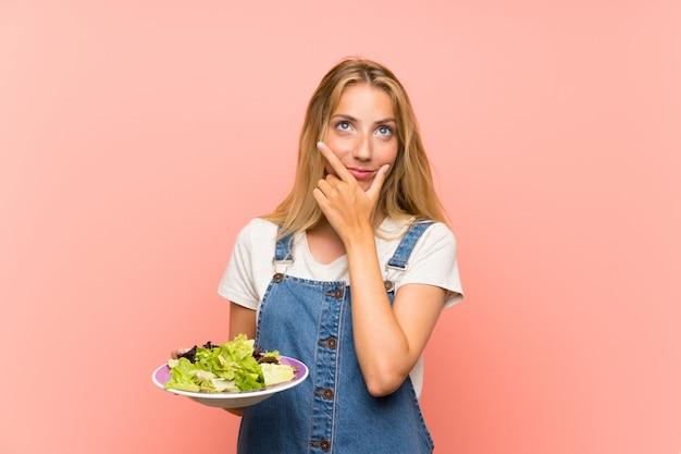 Blondynki Młoda Kobieta Z Sałatką Nad Odosobnioną Menchii ścianą Myśleć Pomysł Premium Zdjęcia