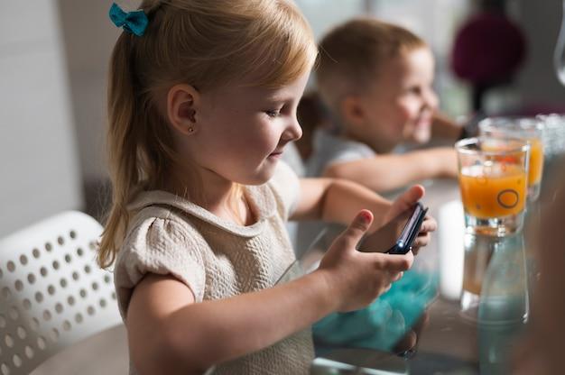 Boczne dzieci bawiące się smartfonami Darmowe Zdjęcia