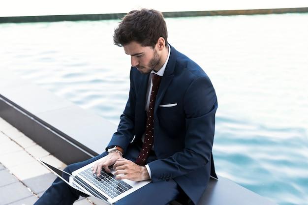 Bocznego widoku mężczyzna pracuje na jego laptopie Darmowe Zdjęcia