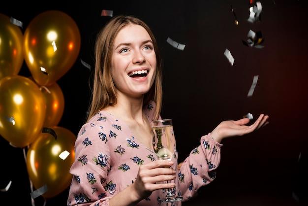 Bocznego widoku smiley kobieta trzyma szkło szampan Darmowe Zdjęcia