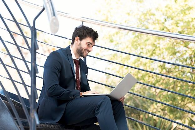 Bocznego widoku smiley prawnik pracuje na laptopie Darmowe Zdjęcia