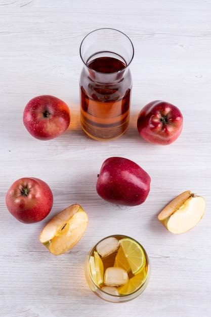 Bocznego Widoku Sok Jabłkowy Z Czerwonymi Jabłkami Na Białym Drewnianym Stole Darmowe Zdjęcia