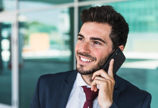 Bocznego widoku szczęśliwy mężczyzna z jego smartphone Darmowe Zdjęcia