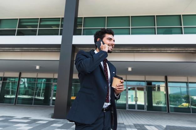 Bocznego widoku szczęśliwy prawnik opowiada na telefonie outdoors Darmowe Zdjęcia